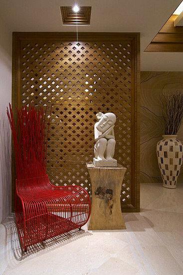 设计师以镂空格纹屏风界定出玄关意象,红色编织造型椅搭配特色雕刻装饰,成为空间段落的视觉端景