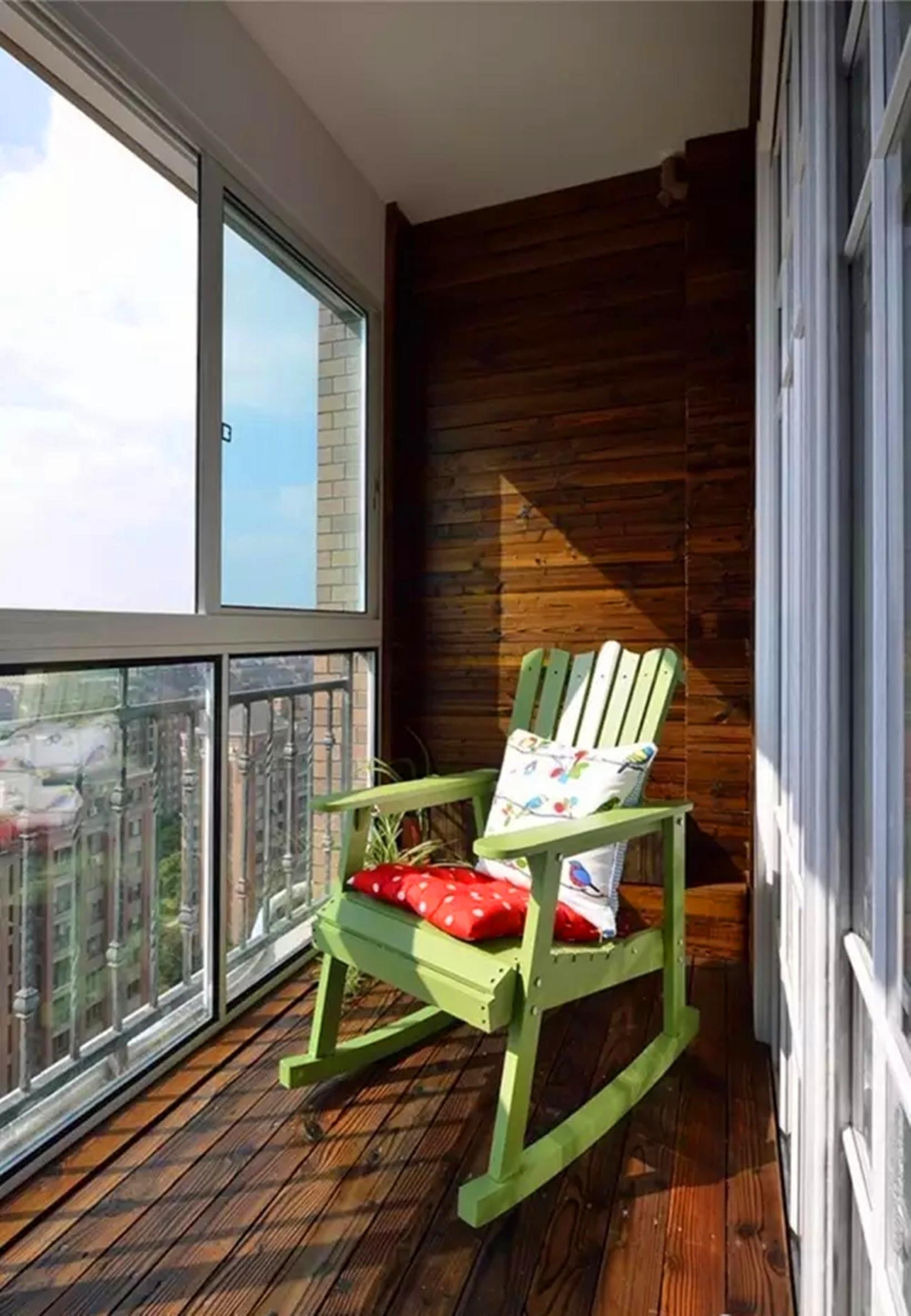 客厅外的休闲阳台用防腐木铺贴墙面和地板,坐着摇椅享受清晨的阳光