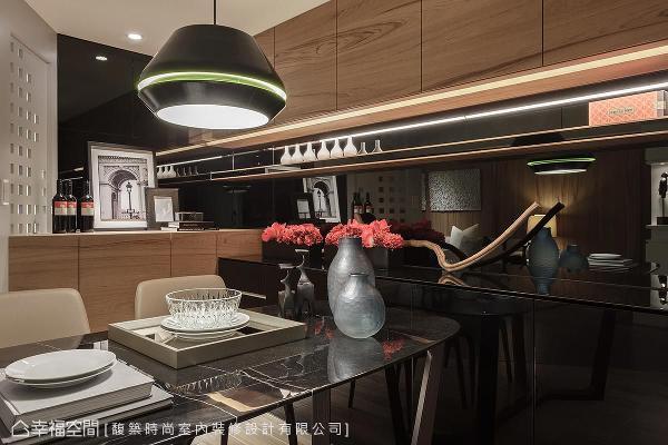 馥筑时尚室内装修设计以黑钢烤及黑镜,让餐厅立面拥有深邃的视觉意象,而吊柜、平台的整合设计,更提供屋主收纳及展示的空间。
