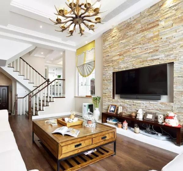 ▲ 文化石铺贴的电视背景墙充满自然风,拆除一楼楼梯间的墙体,让空间更通透