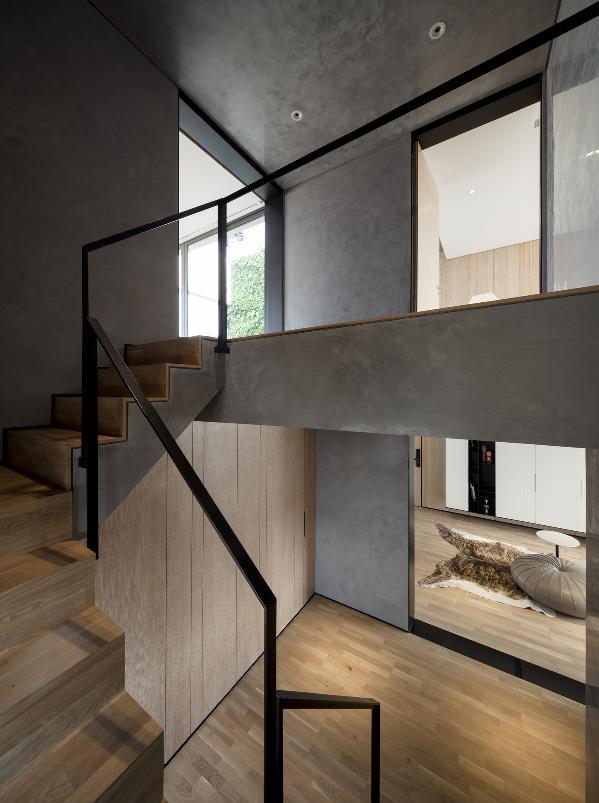 极具肌理感的灰色水泥漆结合硬朗的扶手栏杆使空间有很强的现代感,楼梯踏步的木本色又将水泥色的冷度拉回一定的平衡,空间与材料之间的衔接细节也相应体现。