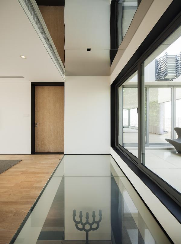 雾化玻璃的应用增强一楼与二楼的互动关系,也可以将天台的采光引入一楼入口玄关处,顶部利用高低关系将伸降式电动遮光帘藏于其中,与雾化调光玻璃的两者结合保证主卧的私密性,顶部的镜面让空间有延伸错觉感。