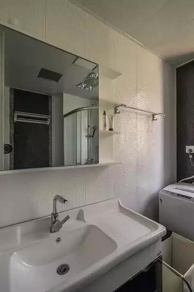 主卫没有过多的颜色搭配,淡米色的仿古瓷砖及简约黑白配的台盆柜,现代气息十足。灯光呈现的明暗阴影,使空间更显柔和,并弥漫着娴静浪漫的气息。