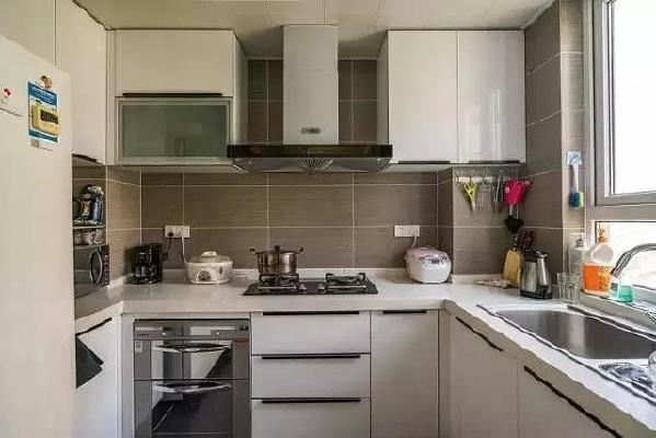 厨房间的布局很合理,U型的橱柜让厨房的每一寸空间都得到充分利用。 亮光的晶钢板门板让厨房空间更显大气。