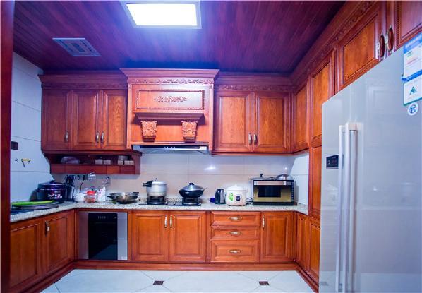 厨房的色调与客厅餐厅整体相统一结合。深色的古典红木家俬橱柜的组合看起来又不那么的严肃。