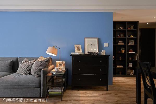 沙发后的灰蓝色墙面,让家人在此谈心聊天时,心情有沉淀、宁静的作用;入门即可见到的端景柜,在心灵层面上有欢迎家人回家的功能。