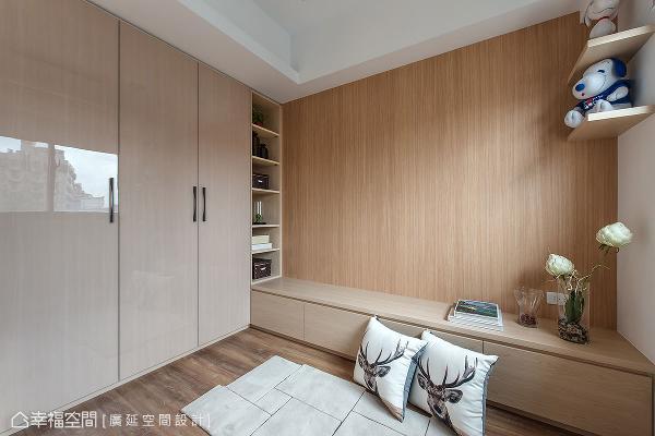 以壁纸呈现出仿木质纹理,与收纳柜亮面水晶板带来对比效果;木作矮柜可作为床头柜,并铺设木地板方便访客打地铺。
