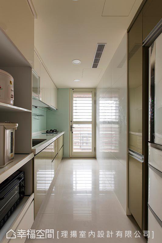 明亮、通风的厨房场域,利用系统柜体收纳大型家电,打造利落宽敞的立面空间。