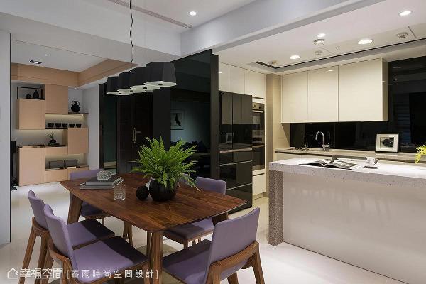 玄关镜面墙延伸至厨房场域,巧妙地隐藏了大型家电,并使用系统柜体收纳,打造干净利落的活动空间。