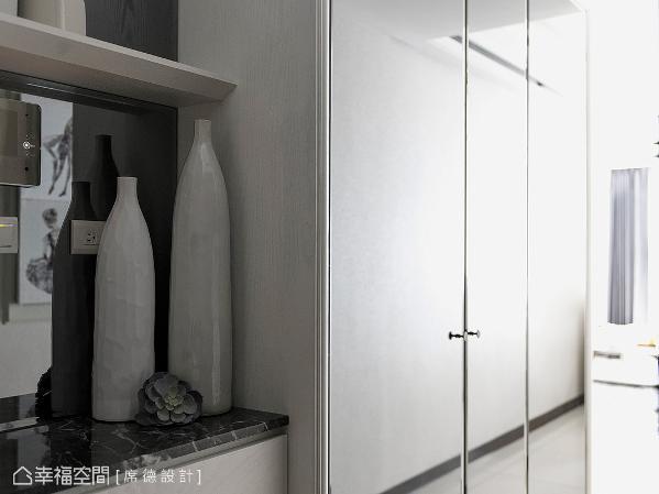 在玄关区的表现上,席德设计团队设置大理石平台,方便屋主放置生活小物或端景收藏,旁侧则规划大容量的收纳鞋柜。
