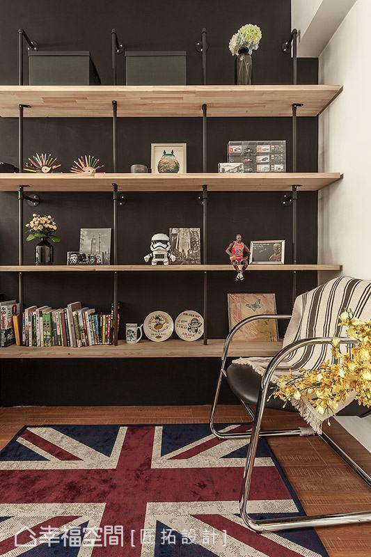 墙面利用深灰色饰底,搭配以原木拼接板与水管造型打造而成的开放展示柜,简单摆放书籍或是趣味小物,成为书房内质感别具的主题端景。