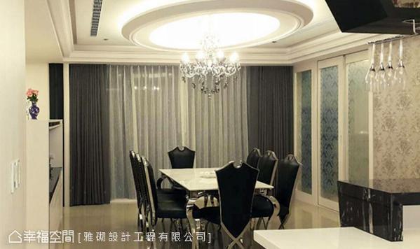 天花板以双心椭圆造型设置间接照明,中间吊挂一盏水晶吊灯做为主灯;搭配一道双面设计的中岛柜,界定出客厅和餐厅空间,也带来展示兼收纳的餐边柜功能。