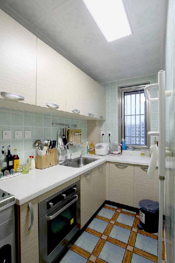 清爽的蓝色墙地砖,米白色橱柜。厨房面积不大,营造出浪漫温馨的感觉。