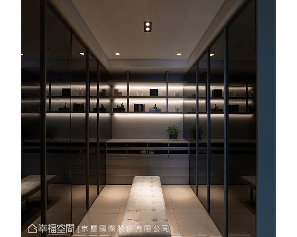 两侧使用灰镜双开门设计,带来连续性的立面造型,修饰衣柜藏物机能。端景墙以适度的灯光氛围照映出裱布板的低调奢华,形塑出精品店VIP室独有的高端订制美学。
