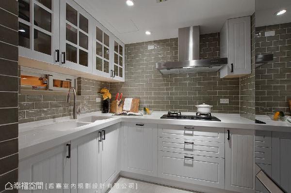 墙面铺贴灰绿色磁砖创造视觉焦点,藉由晶亮的表面折射光线,让不大的厨房空间拥有放大的视觉效果。