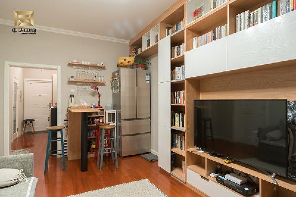 将餐桌改为吧台,利用走廊的空间安置吧凳,将冰箱与连体书柜结合,弱化冰箱的体积感。吴先生和小胡同学都喜欢旅行,玄关的照片墙多数是旅行途中随手拍摄的照片。