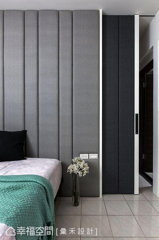 蔡林冲设计师以绷布双色跳的技法打造主卧室精美的床头造型,一并整合右侧的更衣间入口。