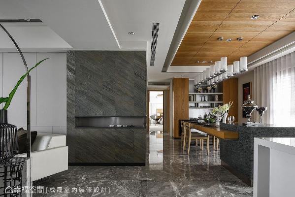 成晟设计在客厅沙发背墙右侧转角,使用拓彩岩包出九十度转角的材质衔接,加上餐厨区上方的木质天花板,隐喻空间属性的转换。