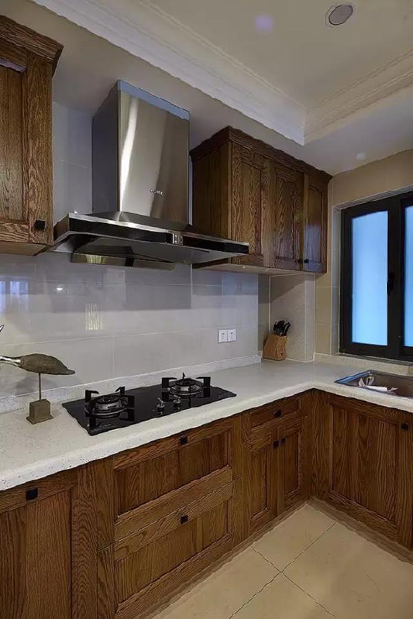 厨房橱柜近照。高吊柜增加收纳空间,与抽油烟机同一条直线安装,整齐有序,化解了抽油烟机的突兀感和厚重感。