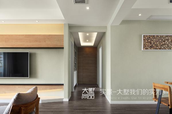 过道底端是主卧套房的进门区,为了考虑一进门不直对着主卧门,在门款式的选择上,我们用了地板上墙,做了隐形的处理,还是延用了电视背景墙上的材质,让空间变大。