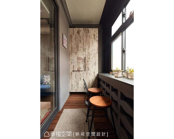 铺设南方松地板,并摆放高脚椅打造出吧台区,让屋主可以一边喝咖啡一边悠闲欣赏风景。墙面利用系统柜规划鞋柜,藉由仿木质斑驳纹理,呈现出经岁月淬炼后留下的历史痕迹,成为入口视觉端景。