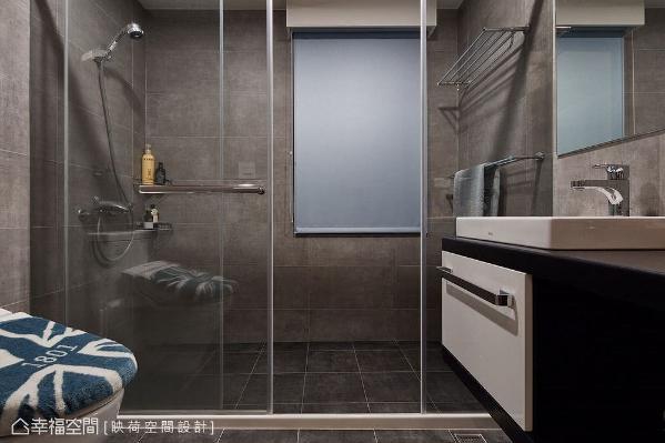 利用通透的玻璃媒材做隔间,创造出干湿分离设计,壁面清一色使用磁砖带来灰色造型,藉由黑白配色浴柜、洗手台及英式风格马桶盖跳脱单一色彩。