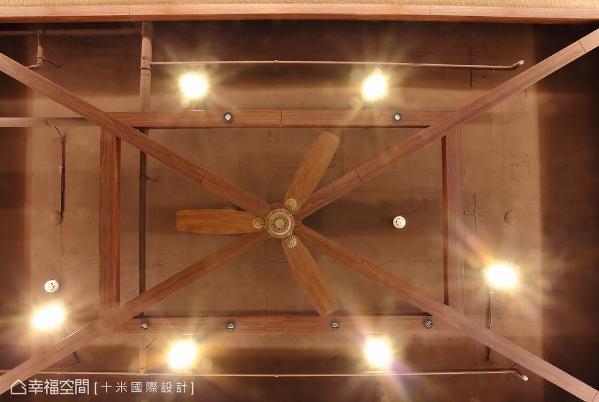 以原木条搭构天花造景,呈现度假小屋的斜屋顶意象,顺势让吊扇融于造型中。