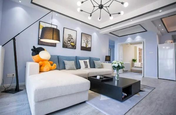沙发边背景墙刷成淡淡的蓝色,然后用一组挂画装饰;