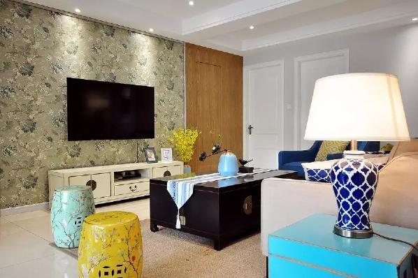 客厅电视墙贴上整面文中儒雅的壁纸,搭配上蓝色、黄色的禅意中式鼓凳,实木的中式茶几等韵味元素,整个客厅都实现儒雅端庄大方;电视墙右侧的那扇门,以独特的木质感作为隐形门打造,显得格外的精致优雅;