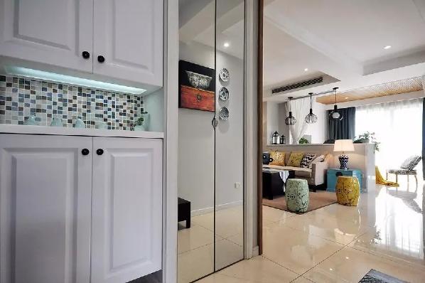 玄关进门后左侧做了个实用情调的鞋柜,在鞋柜中间留空位置贴上马赛克,鞋柜往里是一个高柜,柜门以镜面打造,可以作为玄关里一个实用的镜子;