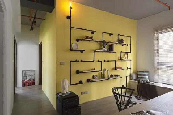 墙面漆成了黄色,与黑色水管书架形成强烈对比。