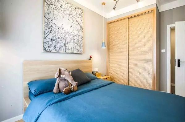 同时,次卧则采用蓝色的床单,背景同样是树枝挂画,进门的推拉门的大衣柜,颜值还是很高的嘛,悬挂的小吊灯也很有趣哦。