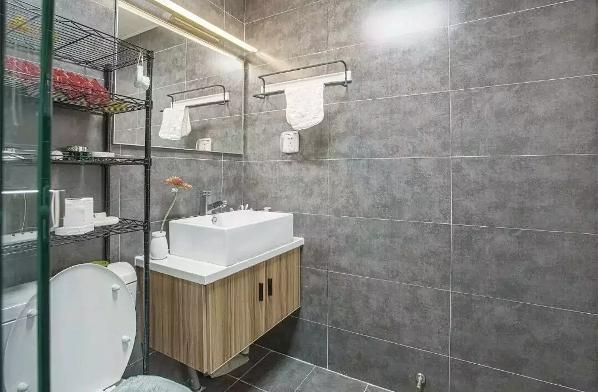 卫生间地面及墙面是水泥砖墙,这样的设计让空间看起来更大了,有没有?还有马桶后面的置物架,填补了卫生间的收纳空白,很贴心的设计。