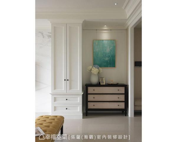 从玄关踏入客厅,跳色的深色柜体和蓝色画作,成为进入公领域的第一道视觉主景。