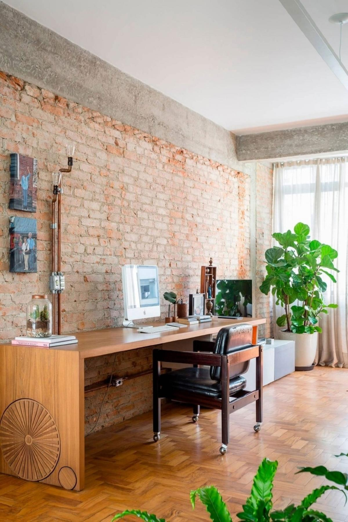 家庭办公室设有8英尺长的定制木桌。它还在电气导管管道的末端设有爱迪生灯泡。