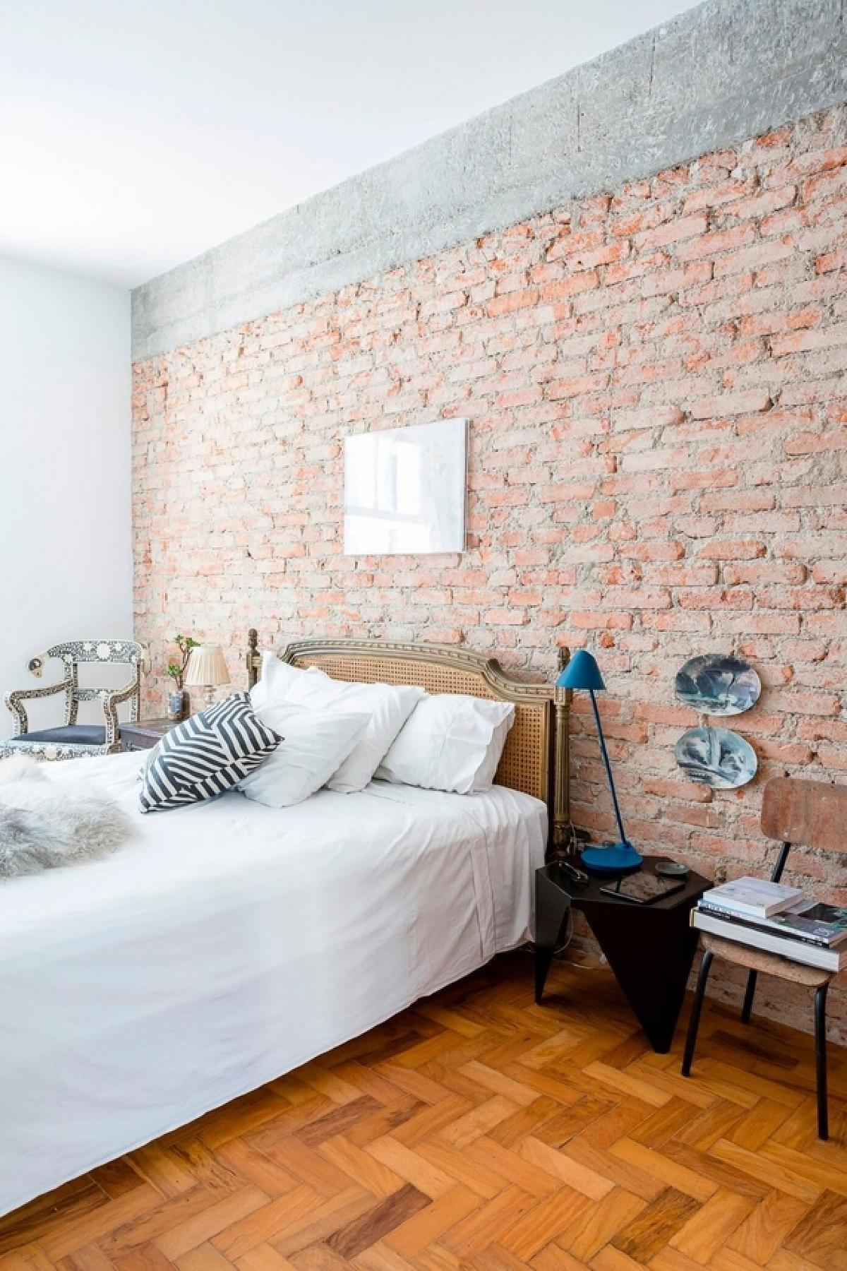 卧室区域保持中立,允许砖砌和原始人字架地板的纹理和图案是主要特征。