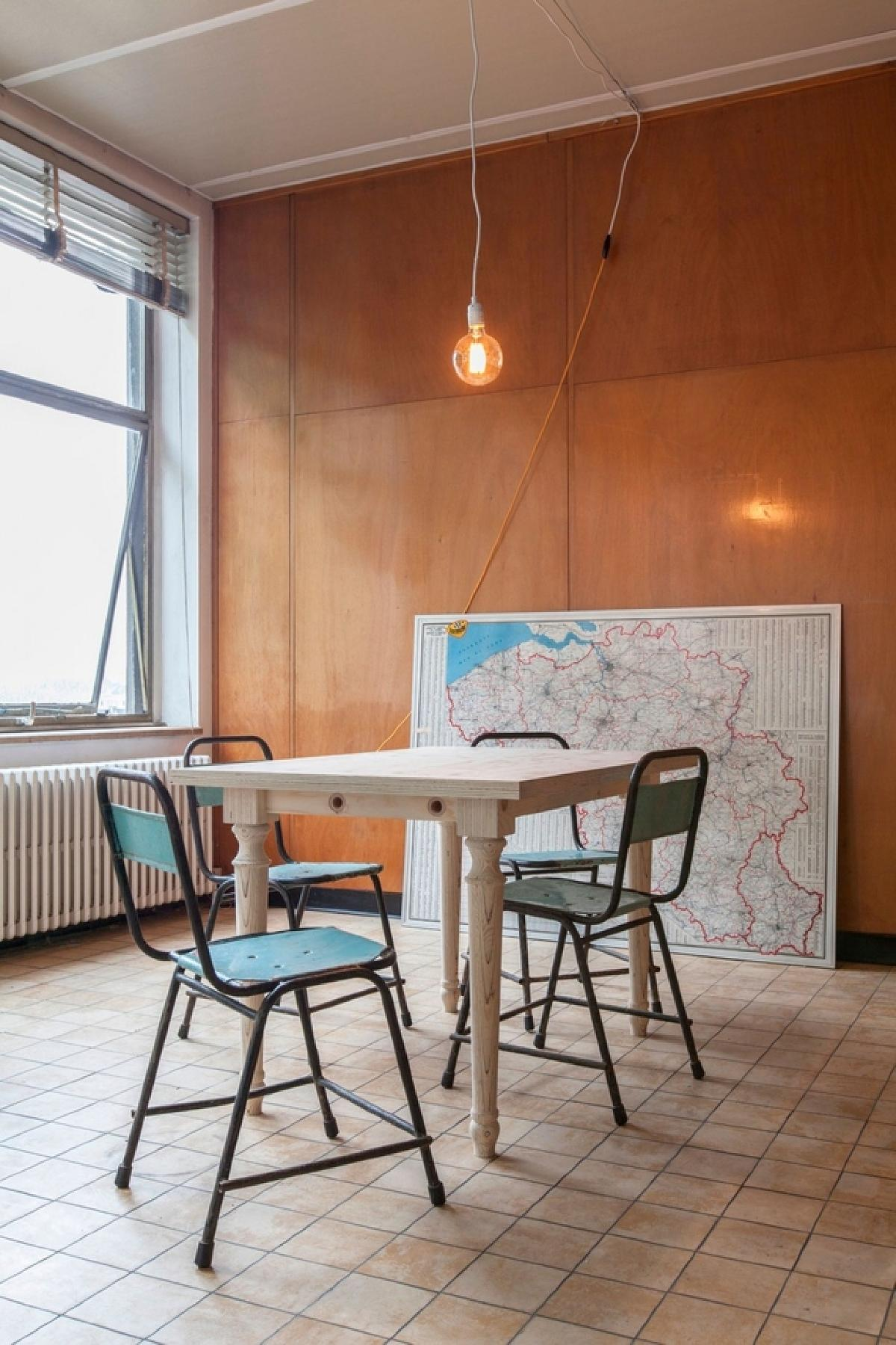 用餐区继续在桌子和椅子,地图和新的但复古的灯光吊坠完整的爱迪生灯泡的复古主题。