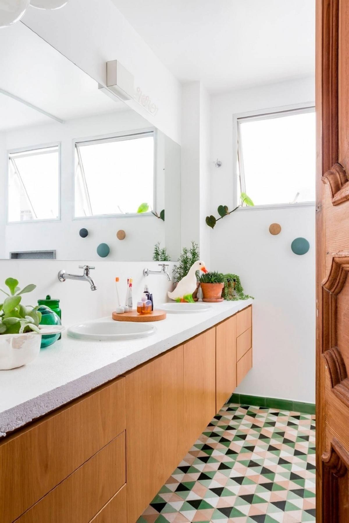 与卧室的中性调色板不同,套间在绿色和粉红色的地板上摇摆着一个充满活力的几何瓷砖图案,由相同配色方案的旋钮毛巾钩来表示。