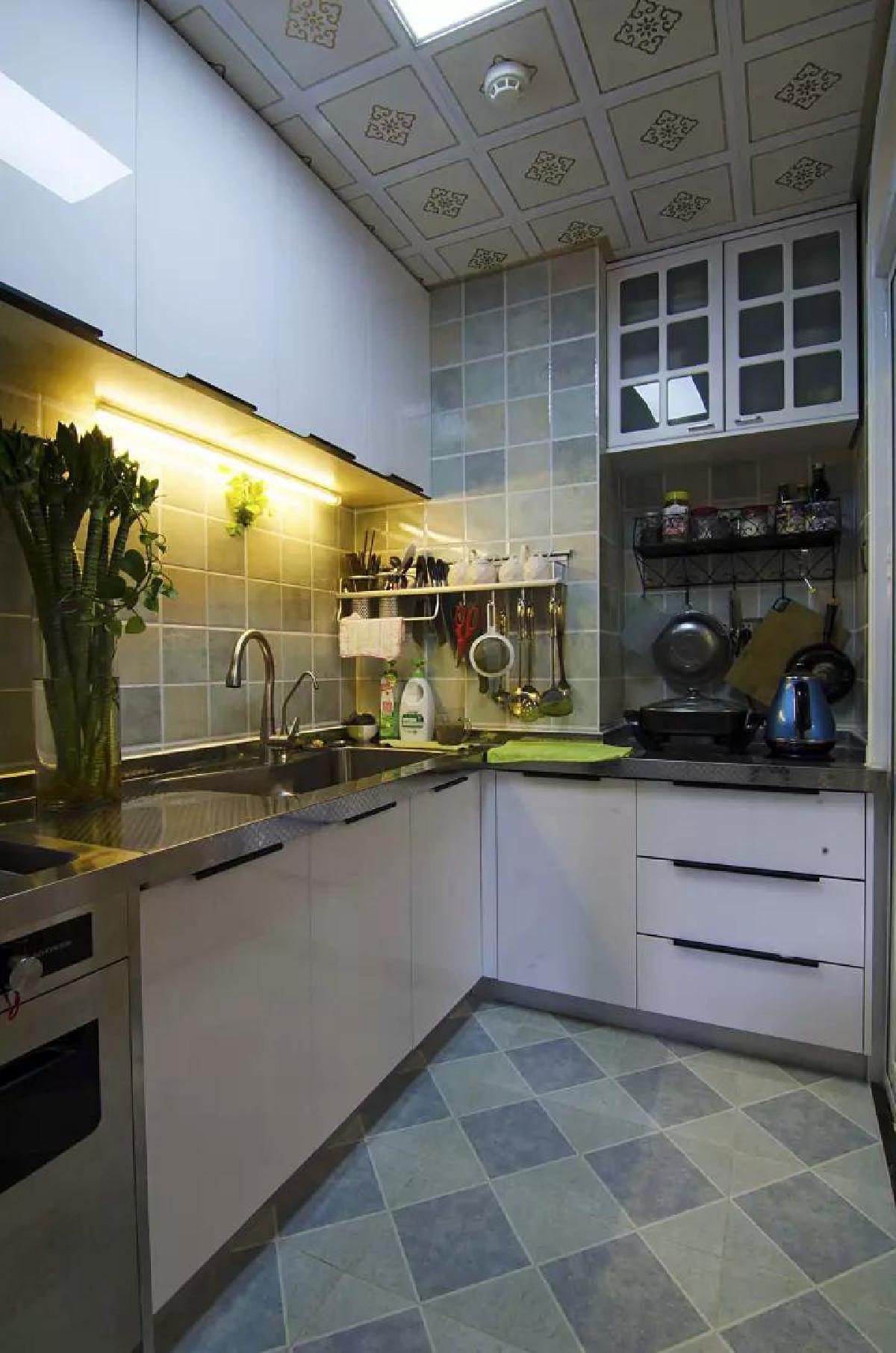 """厨房在橱柜上方也装了逛逛来提升操作台面的光线,避免在洗菜做菜的时候""""黑灯瞎火""""看不清,挂钩上简洁的把各种厨具收纳整齐;独特的多色瓷砖,结合白色橱柜与花色铝扣板,整体简洁又美观"""