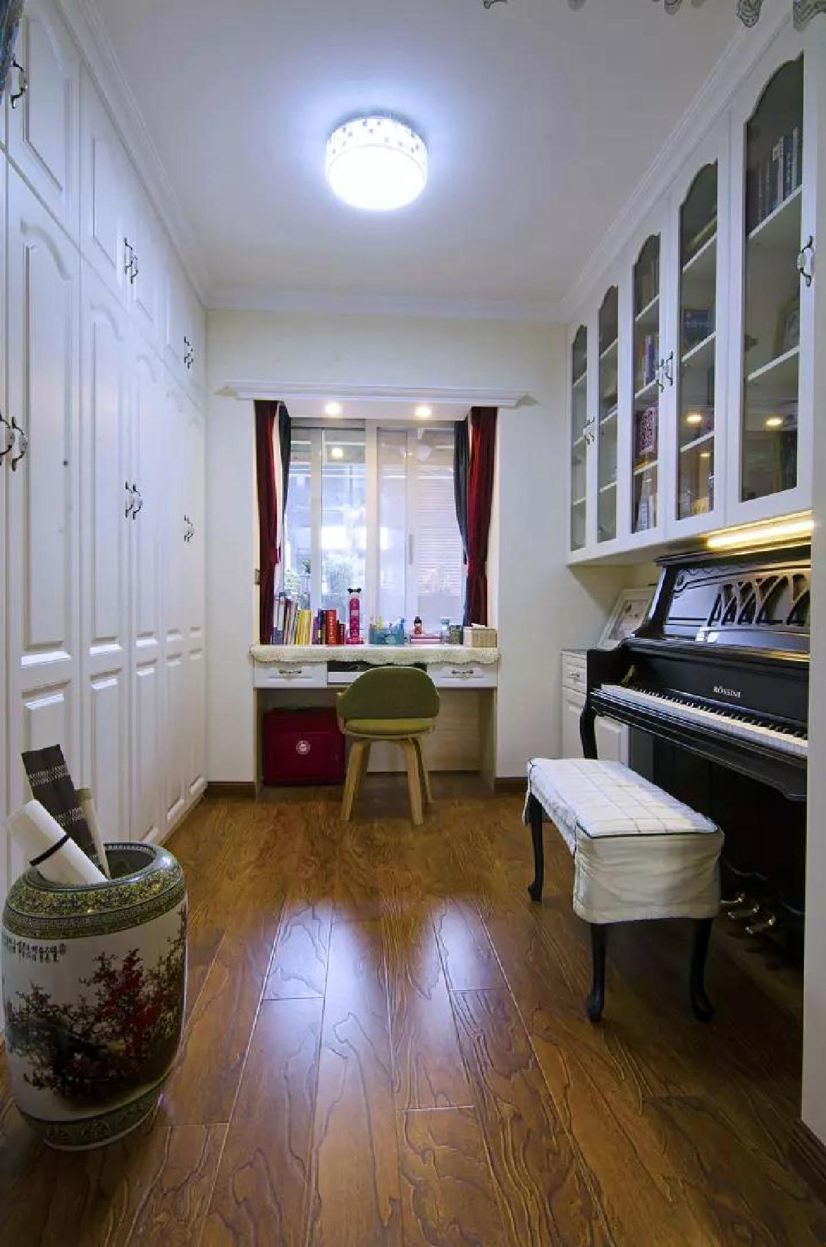 书房里还了一台钢琴,钢琴上方是玻璃门吊柜(用于存放书籍),后方则是大面积收纳柜(可以作为衣物或杂物收纳);同时靠窗装了个悬空书桌,让小书房的功能更加多样化