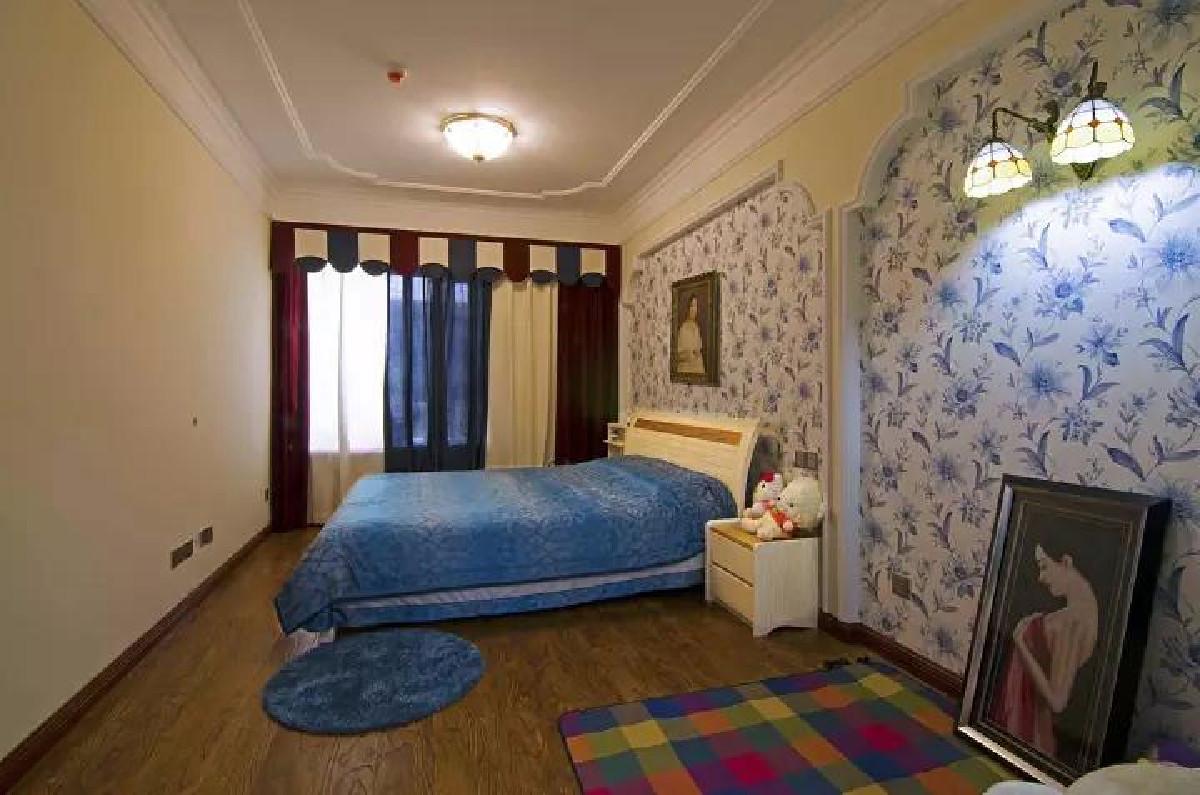 卧室的床头背景墙以蓝色花纹的壁纸铺贴,结合蓝色床与地毯,黑油红蓝白搭配的窗帘,整体充满了热情与浪漫的气息