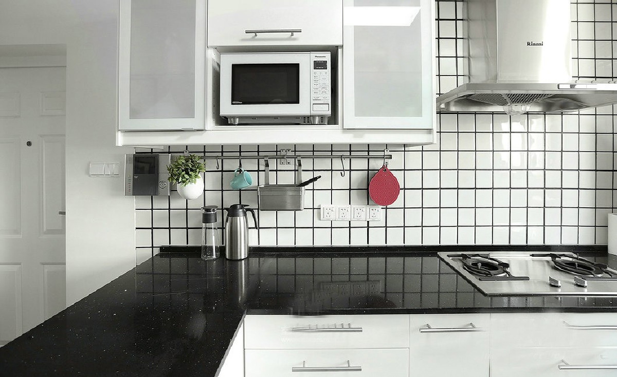 开放式厨房,地砖颜色为灰色,而橱柜的颜色选用较为明亮的白色,整体的