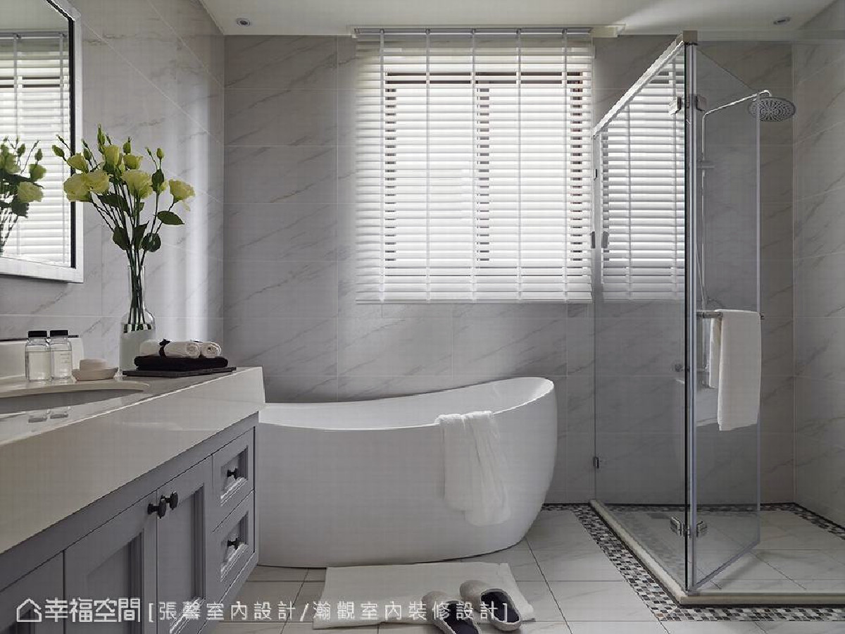 卫浴空间延续整体色调,以干净的灰白色铺垫,并设置独立淋浴间与泡澡浴缸,虽然简单却能感受到家的平实温暖。