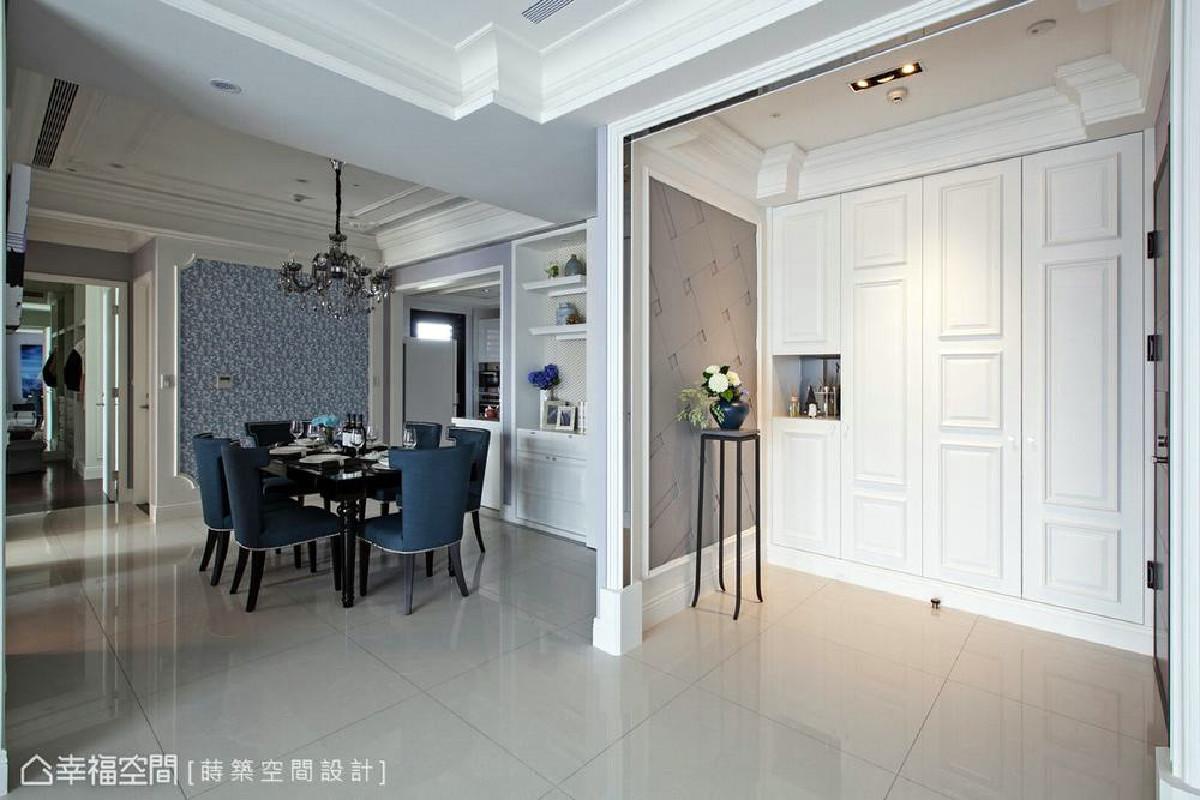 设计师朱皇莳于玄关规划整面式柜体与端景墙,并以门框造型划分与公领域的机能。
