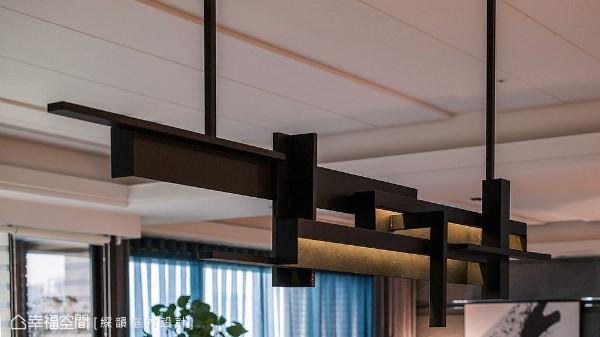 吴金凤与范志圣设计师特别订制金属造型灯具,其切割线条亦延续自壁面与书柜的线条,让整体设计元素有所呼应。
