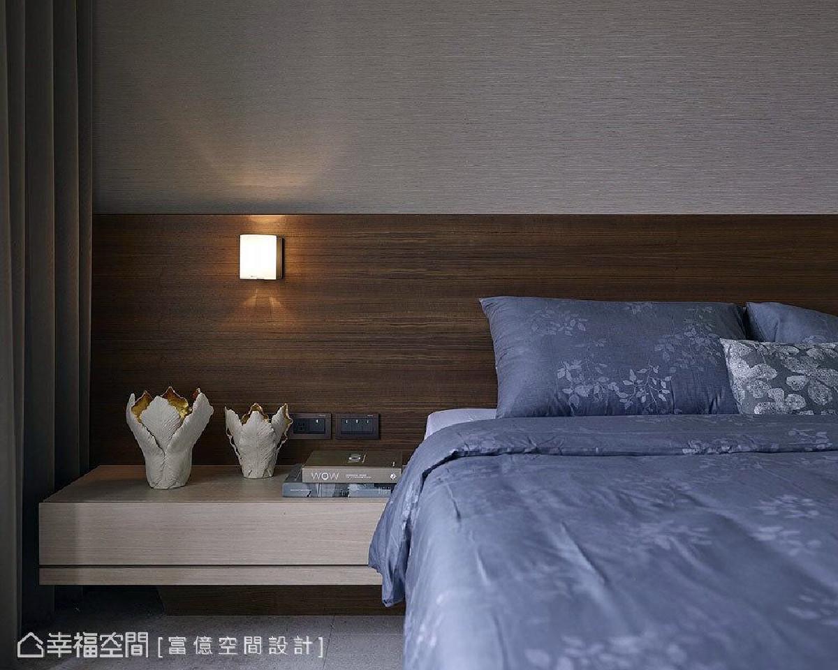 主卧床头墙大面积使用壁布,木纹床头板上装设散发黄光的壁灯,都营造出顶级精品饭店的精致质感。