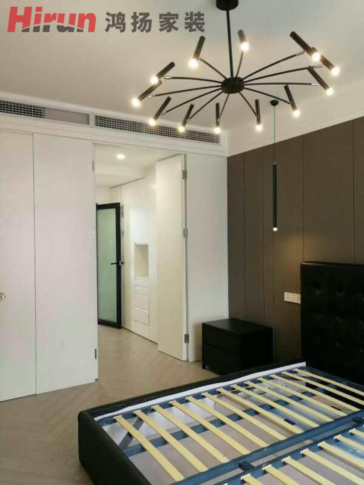 深灰色的现代简洁的床头背墙,造型简洁的黑色灯饰.