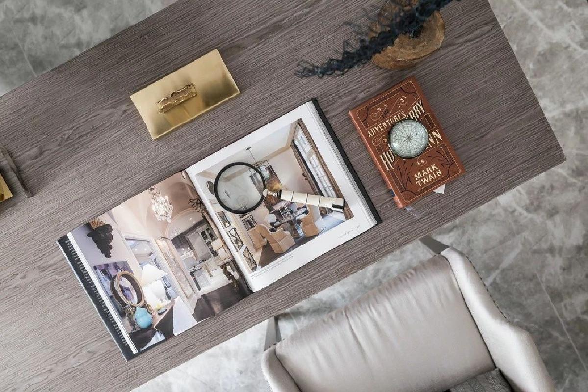 桌案一隅的高明度宝蓝色枝桠和错落分散的几抹橙调则使空间的色彩层次愈加丰富、活跃。