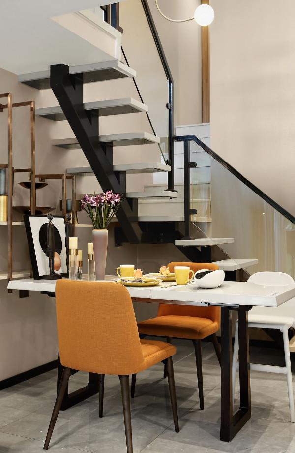 餐厅充分利用客厅、贴墙悬挂式储物架以及通往二层的旋梯之间的空白进行布置,既很好地考虑到了有限的空间运用,同时营造了一个别致温馨的用餐环境。