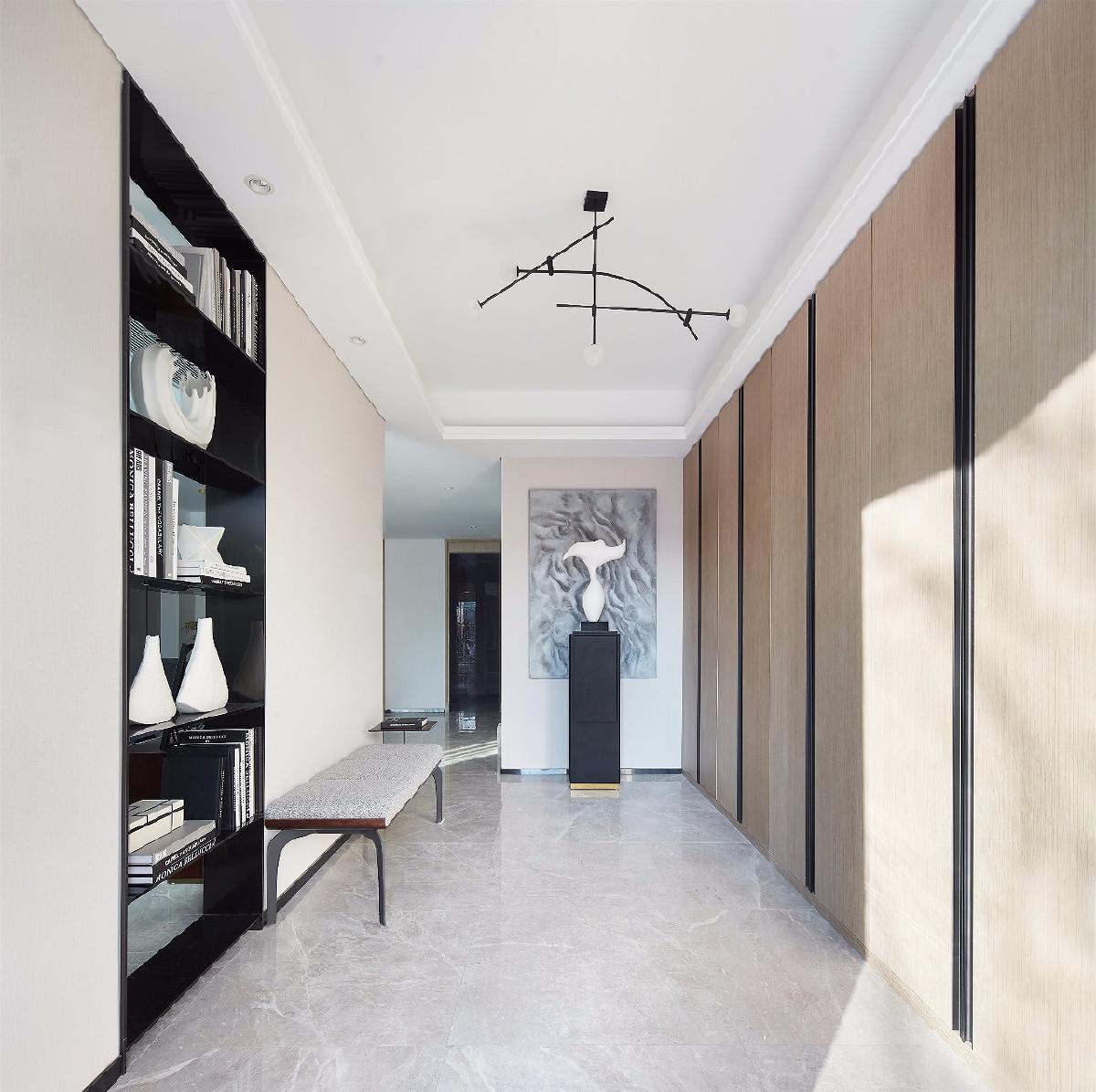 玄关内,长榻、连排收纳柜、独特的雕塑与抽象画,无不散发着令人向往的简约气息。